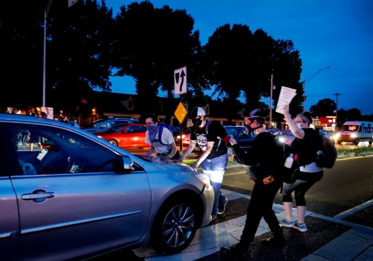 <strong>Protesters block an advancing car on Germantown Road traffic Tuesday, June 2, 2020.</strong> (Mark Weber/Daily Memphian)