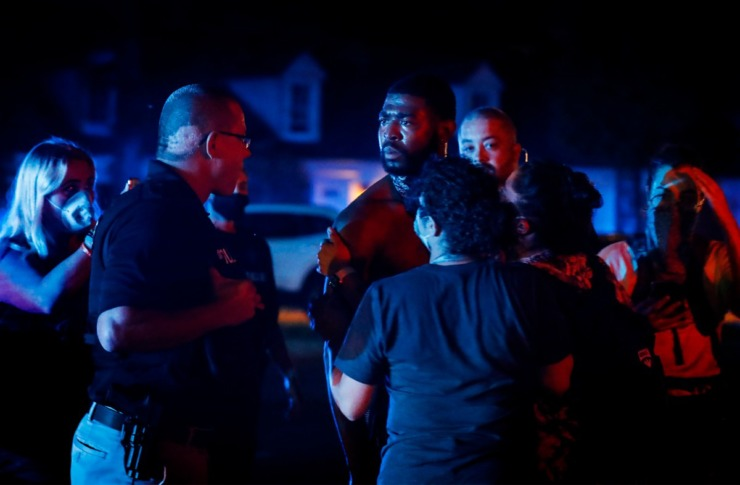 <strong>Activist Darin Abston (right) is held by his friends while speaking to a Memphis police officer after blocking Germantown Road traffic on Tuesday, June 2, 2020.</strong> (Mark Weber/Daily Memphian)