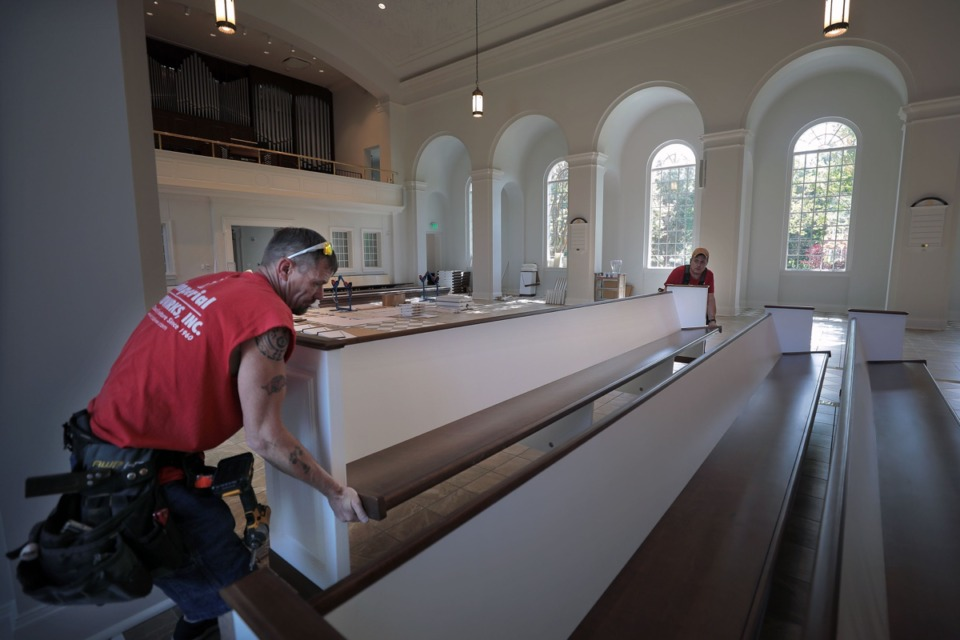 <strong>Tony Hinson (left) and Kevin Smith of Imperial Woodworks move a newly assembled pew into place at Church of the Holy Communion May 26, 2020.</strong>(Patrick Lantrip/Daily Memphian)