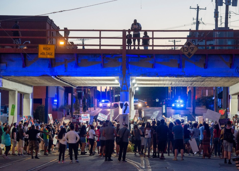 <strong>A father and his two children watch a group of protesters on GE Patterson Ave. as they move under the railroad bridge marching towards Main Street Saturday night, June 6, 2020.</strong> (Greg Campbell/Special for The Daily Memphian)