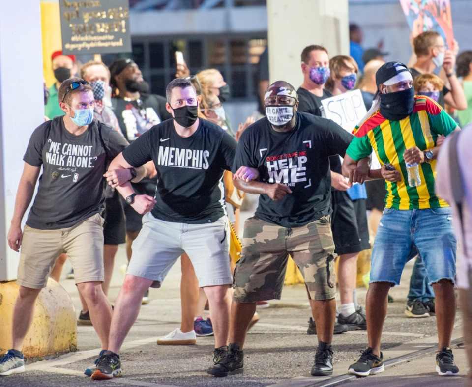 <strong>A group of protesters pause and lock arms under the train bridge at GE Patterson Blvd near Main Street Saturday night June 6, 2020.</strong> (Greg Campbell/Special for The Daily Memphian)
