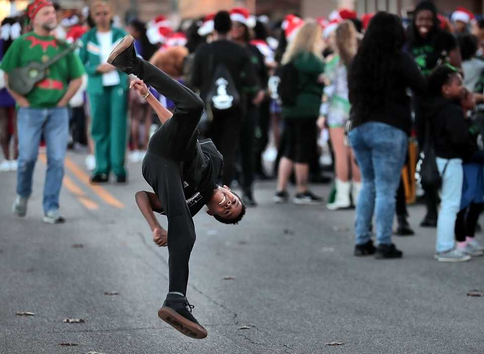 <strong>Jyron Jackson, 11, practices his tumbling before the start of the 2018 Memphis Holiday Parade on Beale Street on Dec. 1. Though the parade was delayed due to the late-running St. Jude Memphis Marathon that took place Saturday Downtown, it didn't deter thousands of Memphians from lining Beale to watch dancers, bands, floats, motorcycles and Santa usher in the holiday season. </strong>&nbsp;(Jim Weber/Daily Memphian)