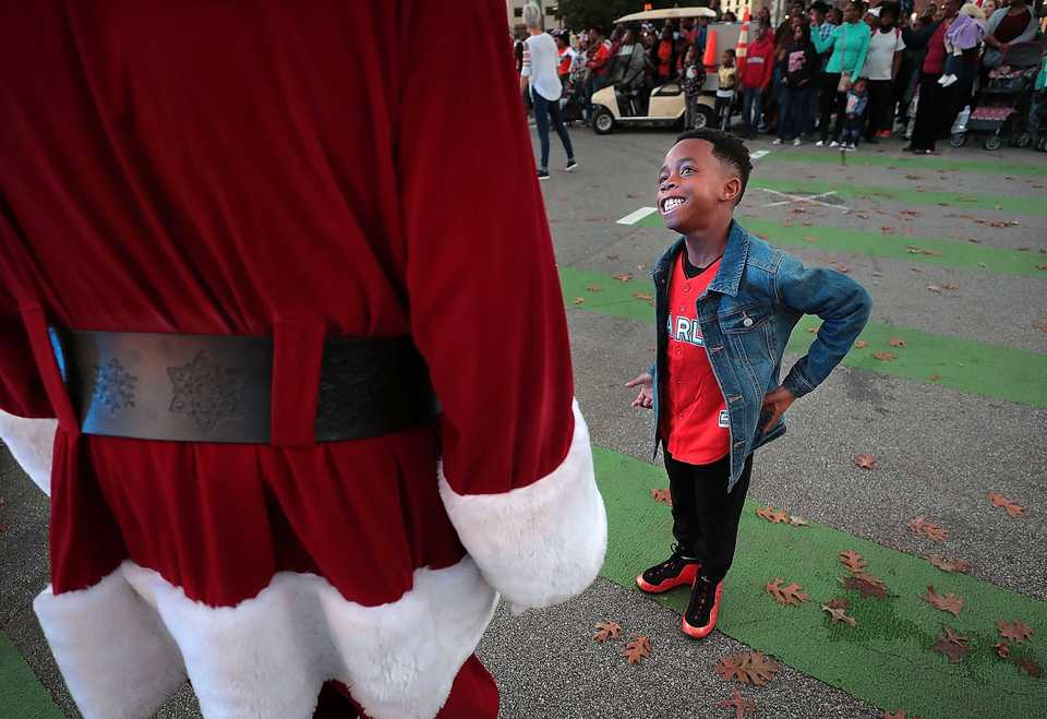 <strong>Omarion Hardy, 7, tries to sneak in some one-on-one time with Santa before the start of the 2018 Memphis Holiday Parade on Beale Street on Dec. 1. Though the parade was delayed due to the late-running St. Jude Memphis Marathon that took place Saturday Downtown, it didn't deter thousands of Memphians from lining Beale to watch dancers, bands, floats, motorcycles and Santa usher in the holiday season. </strong>&nbsp;(Jim Weber/Daily Memphian)