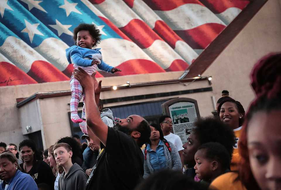 <strong>Alvin Simmons tosses his daughter Miracle Simmons, 1, to keep her entertained before the start of the 2018 Memphis Holiday Parade on Beale Street on Dec. 1.Though the parade was delayed due to the late-running St. Jude Memphis Marathon that took place Saturday Downtown, it didn't deter thousands of Memphians from lining Beale to watch dancers, bands, floats, motorcycles and Santa usher in the holiday season. </strong>&nbsp;(Jim Weber/Daily Memphian)