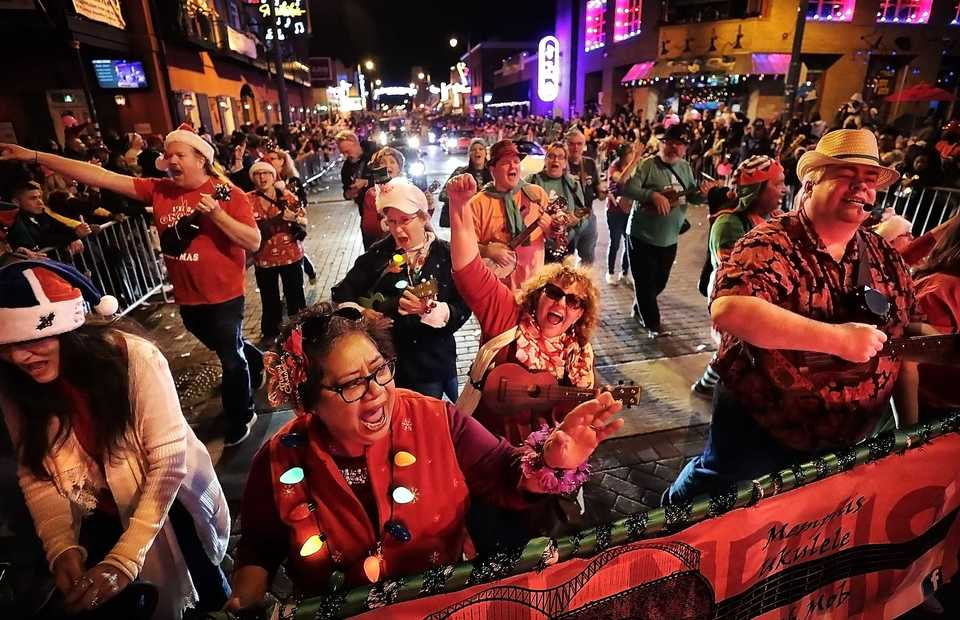 "<strong>Members of the Memphis Ukulele Flash Mob play ""Jingle Bells"" during the 2018 Memphis Holiday Parade on Beale Street on Dec. 1. Though the parade was delayed due to the late-running St. Jude Memphis Marathon that took place Saturday Downtown, it didn't deter thousands of Memphians from lining Beale to watch dancers, bands, floats, motorcycles and Santa usher in the holiday season..</strong> (Jim Weber/Daily Memphian)"
