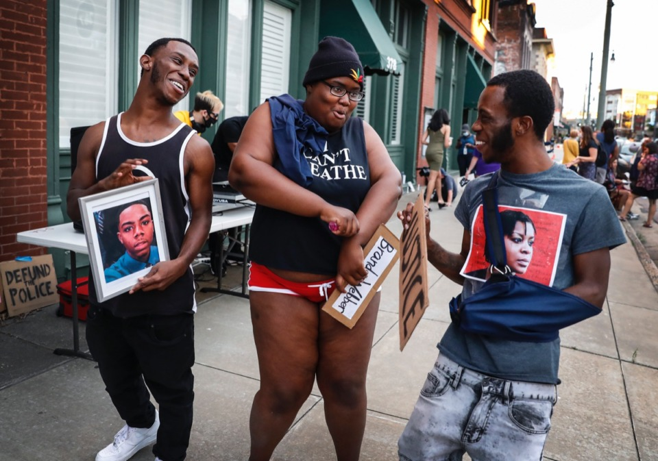 <strong>During a Defund the Police Block Party, while holding portraits of people killed at the hands of the police around the country, Kylan Miller (left) dances with Shannon Franklin, (middle) and twin brother Kameron Miller on Wednesday, June 10, 2020, on South Main.</strong> (Mark Weber/Daily Memphian)
