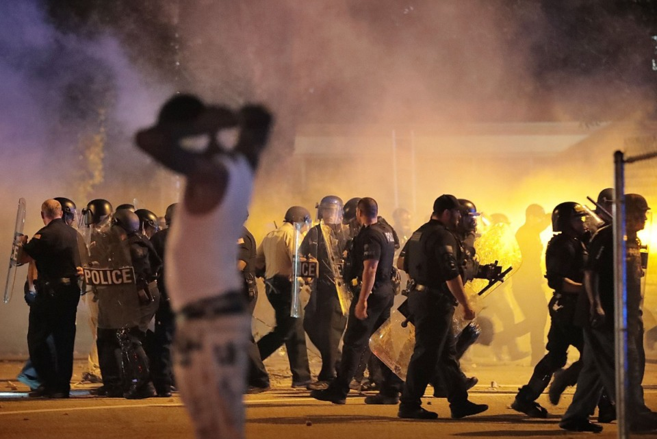 <strong>Police retreat June 12, 2019, under a cloud of tear gas as protesters disperse from the scene of a standoff after Frayser residents took to the streets in anger against the shooting a youth identified by family members as Brandon Webber by U.S. Marshals earlier in the evening.</strong> (Jim Weber/Daily Memphian)