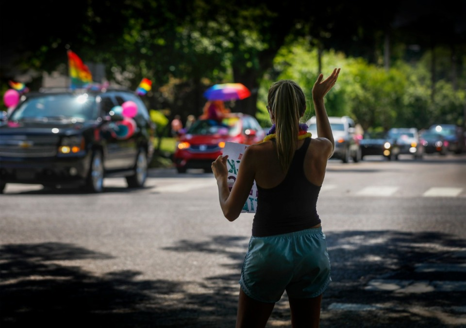 <strong>A bystander cheers on the parade of cars heading through Midtown toward the National Civil Rights Museum.</strong> (Mark Weber/Daily Memphian)