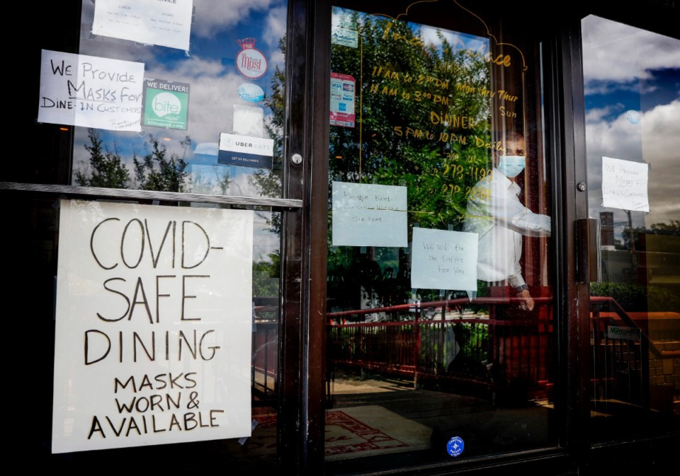 <strong>India Palace owner Binder Kumar (peering out the window of his Midtown restaurant) advertises that his staff follows the Shelby County Health Department mandate of wearing masks. But a survey of 50 area restaurants found that many do not wear masks at all.</strong> (Mark Weber/Daily Memphian)