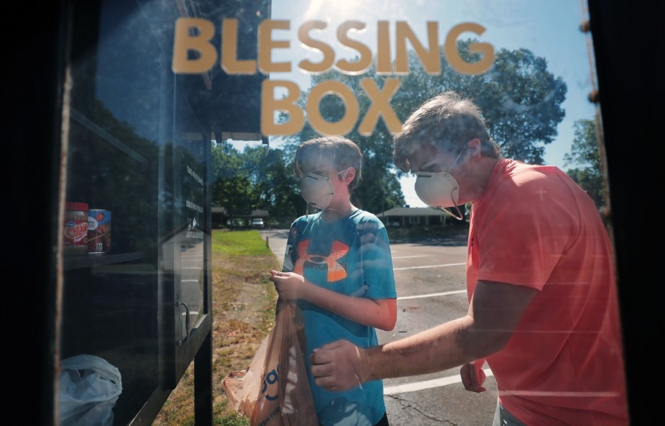 """<strong>Anderson Kreis (left) and his brother Landon stock the """"blessing box"""" with donations at the Arlington Little Free Pantry in the parking lot of Living Word Lutheran Church June 19, 2020.</strong> (Patrick Lantrip/Daily Memphian)"""