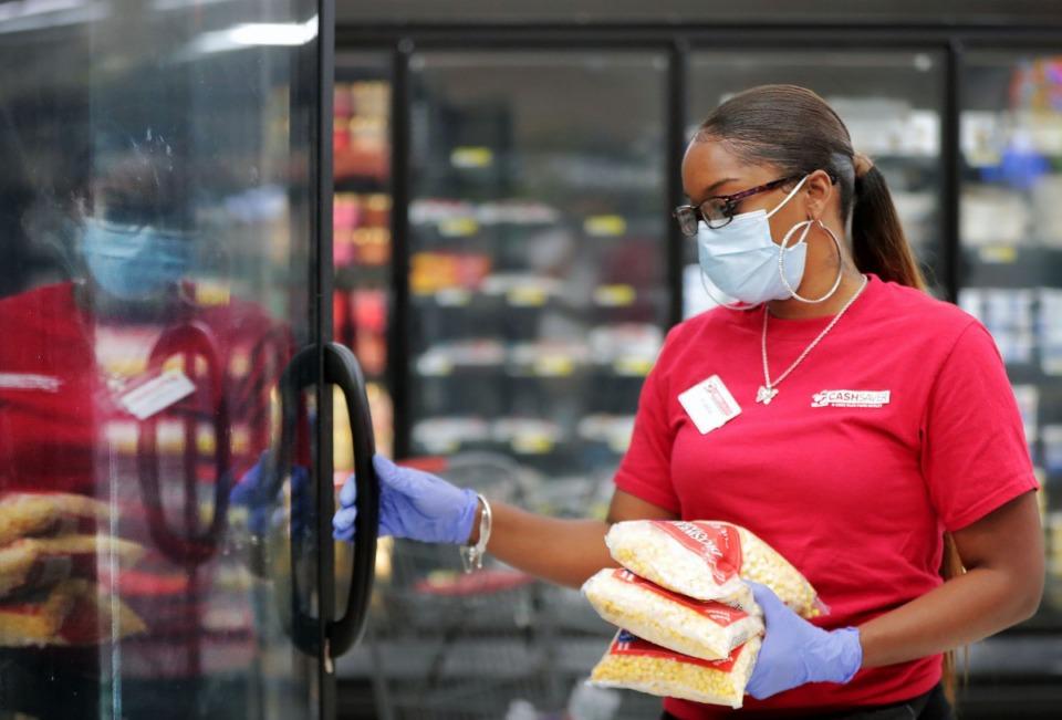 <strong>Cash Saver employee Kiara Jones restocks the frozen food isle inside the Midtown grocery store June 18, 2020.</strong> (Patrick Lantrip/Daily Memphian)