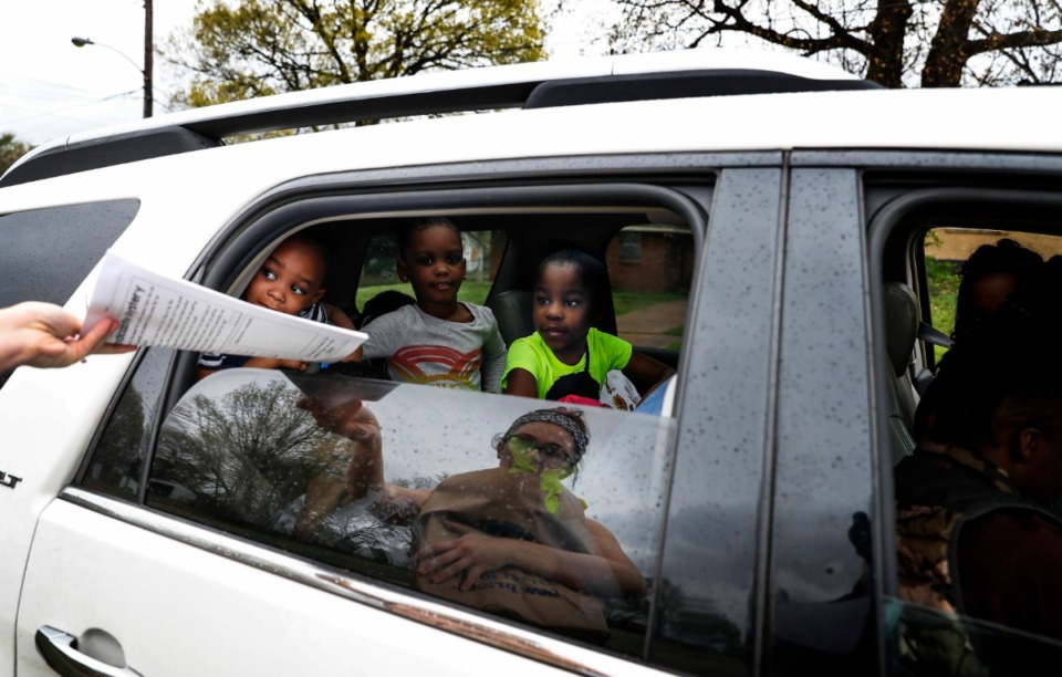 <strong>(left to right) Jerrika Minnis, 3, Jakira Jones, 5, and Paris Moore, 7, grab classwork from first grade teacher Taylor Beardall (reflection) while getting donated supplies at KIPP Memphis Preparatory Elementary school on Friday, March 20, 2020. The school has since been closed.</strong> (Mark Weber/Daily Memphian file)