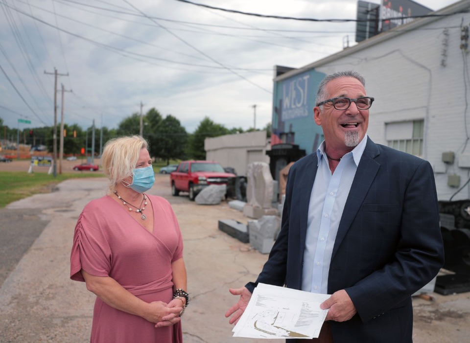 <strong>Paul West (right) and his wife stand in the alley behind West Memorials. The alley, which provides trucks access to West Memorials' loading dock, is the source of the dispute over the proposed gas station that would go into the property behind West's. West claims that the gas-station site plans he's holding would cut off access to the loading dock behind his shop, effectively putting him out of business.</strong> (Patrick Lantrip/Daily Memphian)