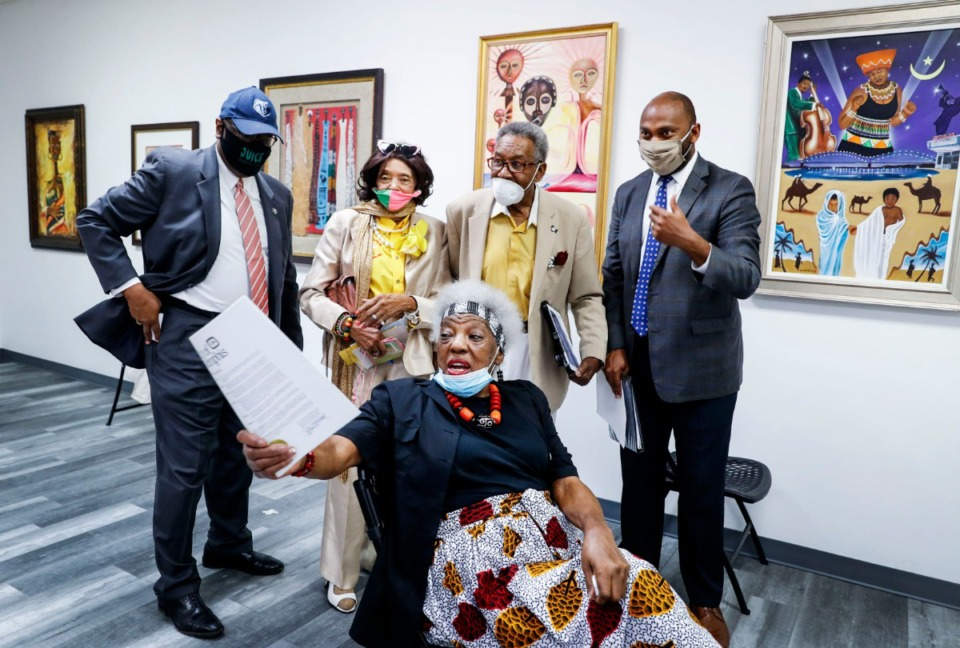 "<strong>Orange Mound Arts Council executive director Mary Mitchell (seated) points out ""Africa in April"" posters to Shelby County Commissioner Reginald Milton (from left), Yvonne Acey, David Acey and Shelby County Mayor Lee Harris during a ceremony on Wednesday, June 24. The Orange Mound Arts Council signed a 50-year lease for the Orange Mound Gallery, renting the property at 2471 Park for free.</strong> (Mark Weber/Daily Memphian)"