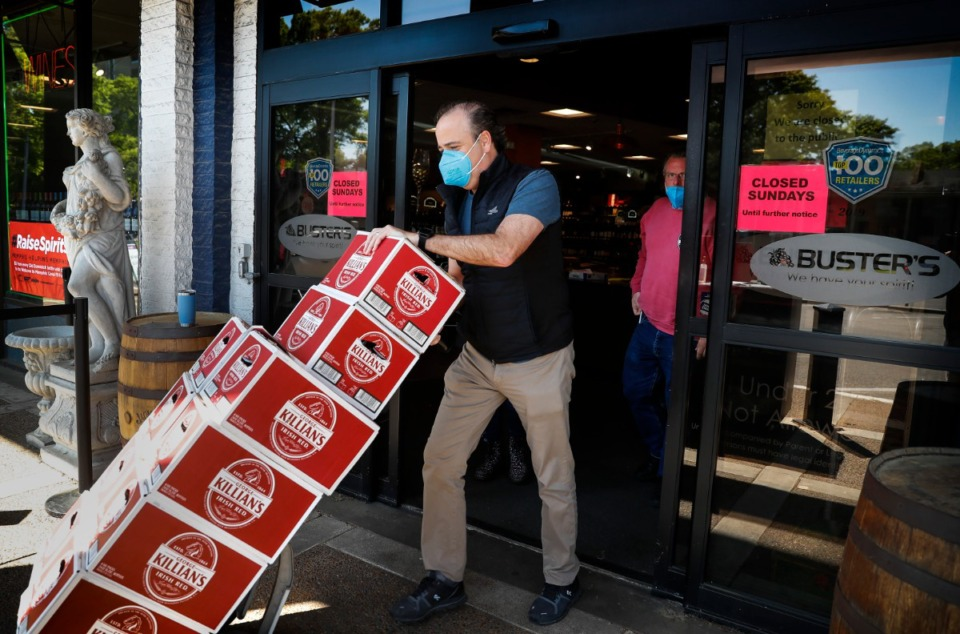 <strong>Buster's owner Josh Hammond delivers an order of beer for pickup on Thursday, April 16, 2020.</strong> (Mark Weber/Daily Memphian file)
