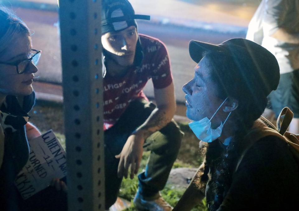 <strong>A group of protesters tend to a young woman who was tear-gassed by Shelby County Sheriff's deputies May 31, 2020, by pouring milk on her face.</strong> (Patrick Lantrip/Daily Memphian)