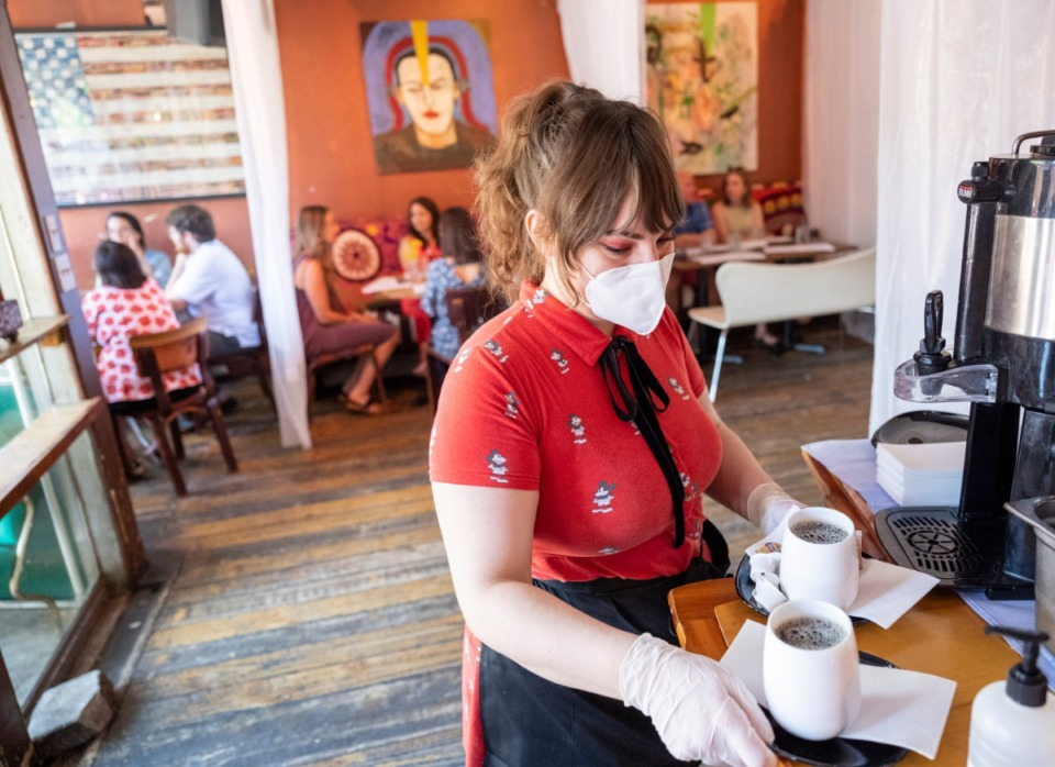 <strong>Sarah Mosley gets the coffee poured and ready to serve in the newly decorated Bar DKDC. Booths are now separated with plastic sheeting to keep social distancing in the restaurant.</strong> (Greg Campbell/Special to Daily Memphian)