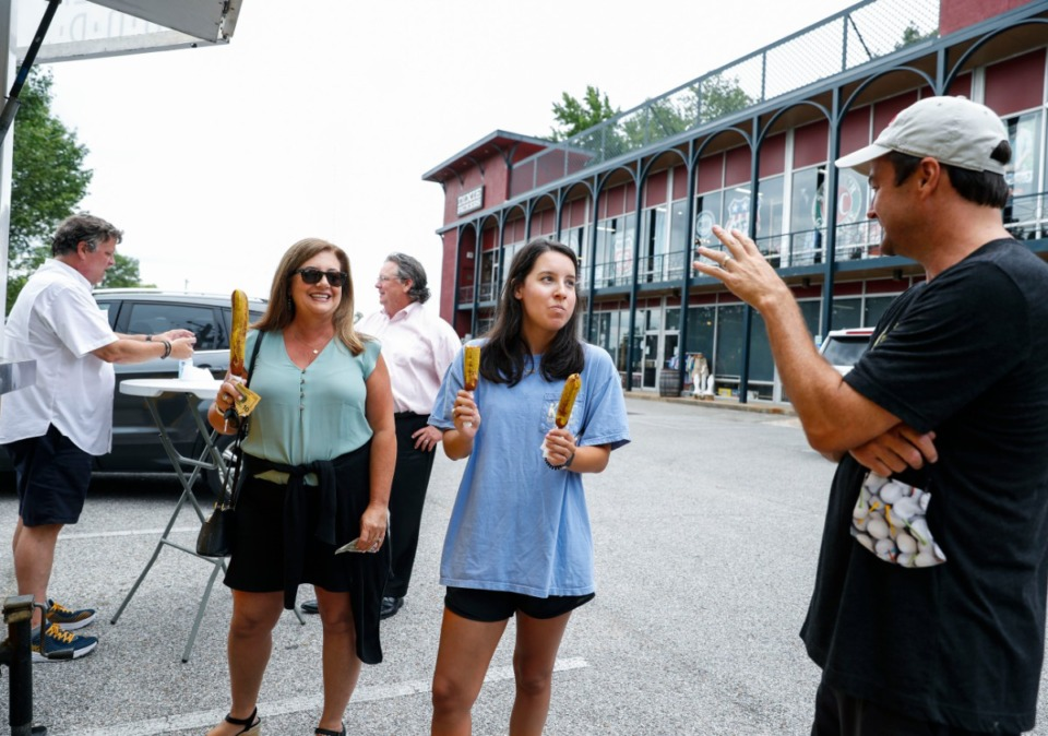 <strong>Kelly Bunch (left ) and daughter Aston Bunch (middle) chat with Sam Almand (right) after buying pronto pups Monday, June 30, 2020. The Pronto Pup truck will be located at the Dixie Pickers this week, opening from 11 a.m. to 6 p.m.</strong> (Mark Weber/Daily Memphian)