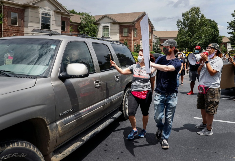 <strong>Protesters confront a man in his truck after they indicated he nearly hit them while they demonstrated in Germantown.</strong> (Mark Weber/Daily Memphian)