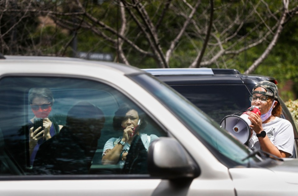 <strong>Memphis Activist LJ Abraham (right) uses a bullhorn confront a man in his truck after the crowd indicated he nearly hit protesters while they demonstrated in Germantown.</strong> (Mark Weber/Daily Memphian)