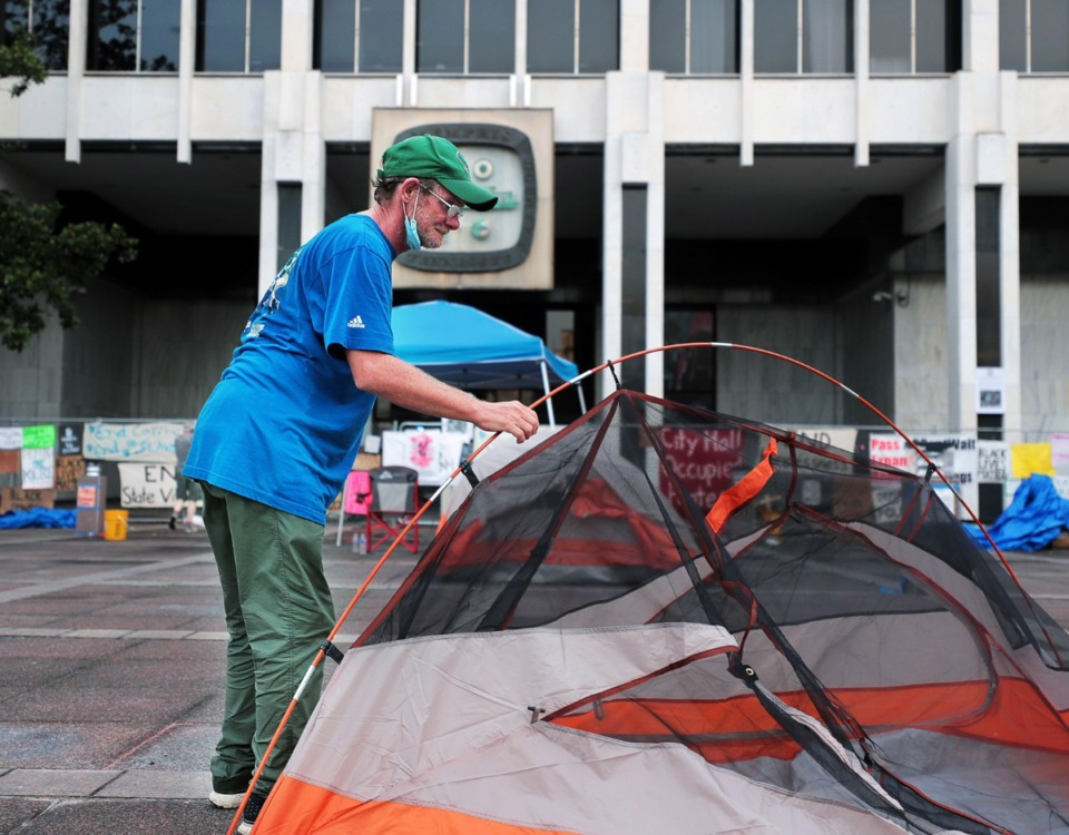 <strong>A man sets up a tent in front of Memphis City Hall June 30, 2020. What started out as a Black Lives Matter protest has evolved into a campaign to feed and provide shelter to Downtown's homeless population.</strong> (Patrick Lantrip/Daily Memphian)