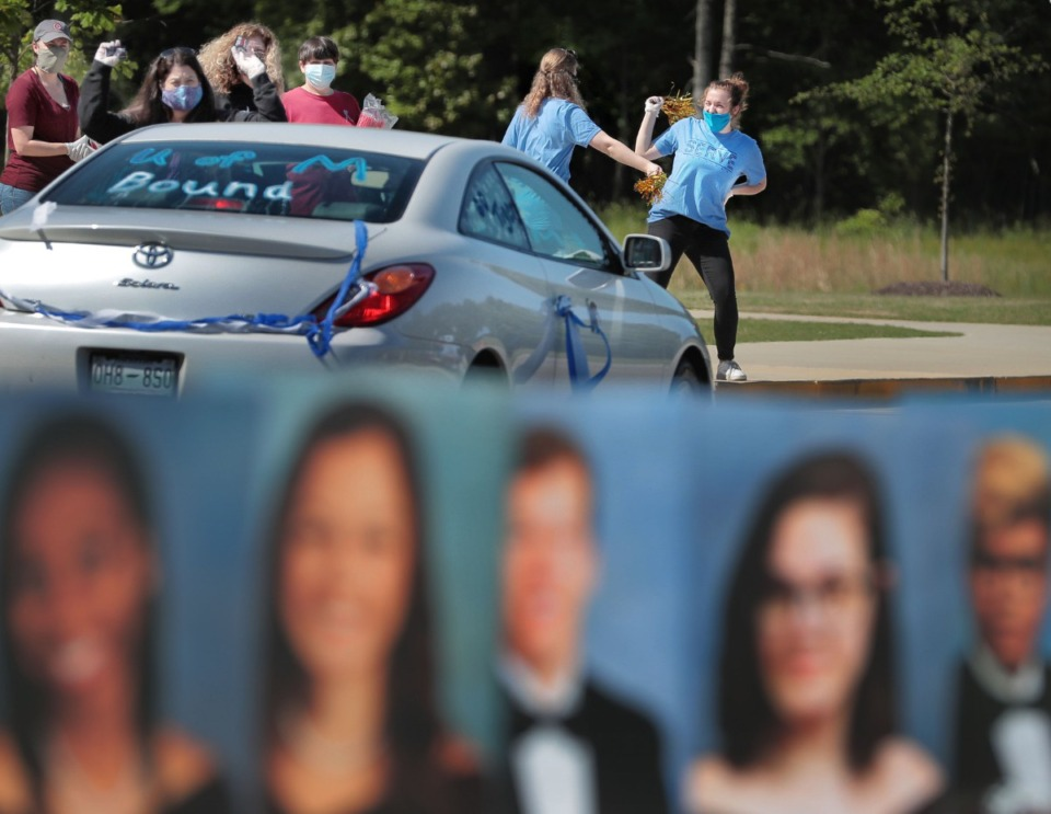 <strong>Volunteers from Collierville First Baptist Church cheer for Collierville High School graduates driving through to pick up their caps and gowns at the school on May 7.&nbsp;</strong><span><strong>&ldquo;Going to school can expose children to greater health risks, but so can staying home,&rdquo; said Le Bonheur Children's Hospital pediatrician Jason Yaun. &ldquo;Many parents are facing very difficult choices.&rdquo;</strong>&nbsp;</span>(Daily Memphian file)