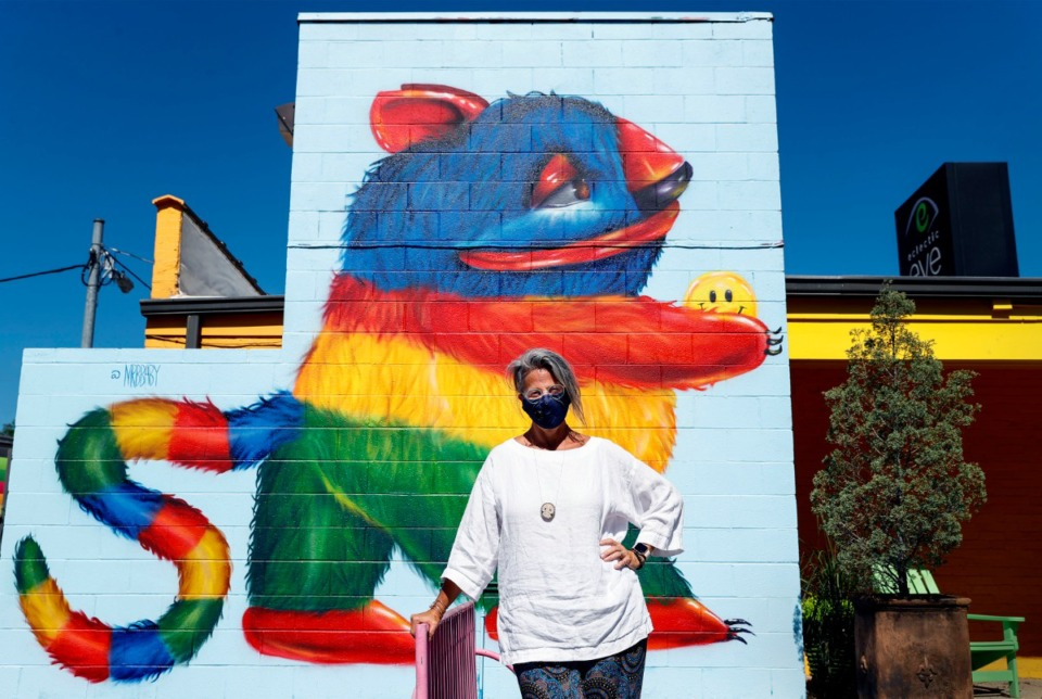 """<strong>Robbie Johnson Weinberg, owner of the Eclectic Eye, stands by her new mural Monday, July 13, 2020. The image on the east side of 242 Cooper St. was painted by Michelle &ldquo;MrBbaby&rdquo; Ruby, who calls the creature 'Chucho."""" It is Ruby's signature design and represents a pinata. </strong>(Mark Weber/Daily Memphian)"""