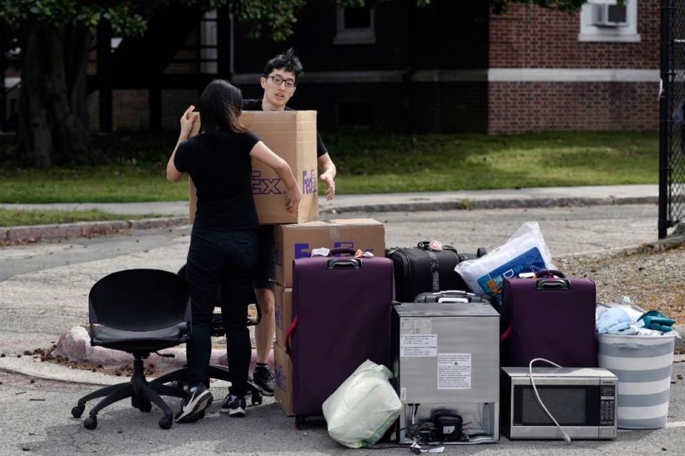 <strong>Duke freshman Feng Cong from Singapore and Cassie Lu from Thailand carry a box of their belongings to a pile as they move out of his dorm at Duke University March 15, 2020, in Durham, N.C. Cong and Lu were returning home since students were being asked to move out and complete classes online for the rest of the semester because of coronavirus.</strong> (Scott Sharpe/The News &amp; Observer via AP)