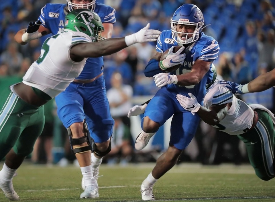 <strong>University of Memphis running back Kenneth Gainwell dodges Tulane defenders during the Tiger&rsquo;s game on Oct. 19, 2019 against the Green Wave at Liberty Bowl Memorial Stadium in Memphis.</strong> (Daily Memphian file)