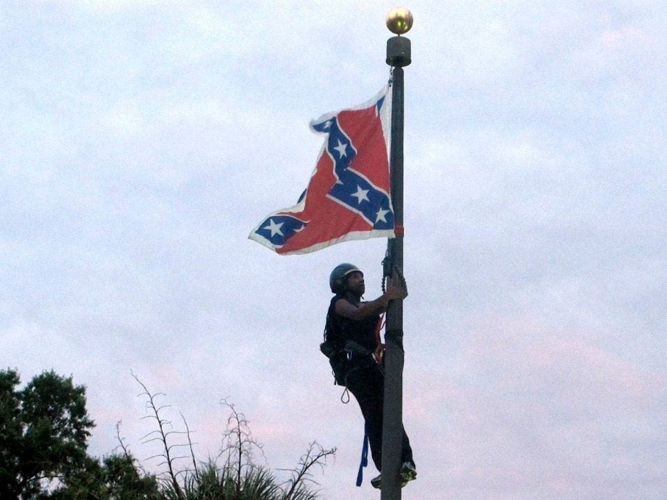 <strong>In this June, 27, 2015, file photo, Bree Newsome of Charlotte, N.C., climbs a flagpole to remove the Confederate battle flag at a Confederate monument in front of the Statehouse in Columbia, S.C. After nine black parishioners were slain at a Charleston church, South Carolina did what many thought would never happen: It moved the Confederate flag off Statehouse grounds.</strong> (Bruce Smith, AP File)