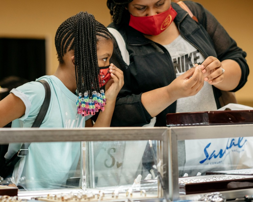 <strong>Ashley Noel (right) shows a ring to her daughter Daelyn Griffin (left) at the Memphis Bridal Show at the Whispering Woods Hotel in Olive Branch, Mississippi. The bridal show moved ahead with its annual event despite the pandemic.</strong> (Houston Cofield/Special the Daily Memphian)