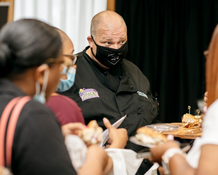 <strong>Chris Hughes, executive chef for Thomas Meat and Seafood Catering, serves barbecue sampler sandwiches to guests of the Memphis Bridal Show at the Whispering Woods Hotel in Olive Branch, Mississippi. The bridal show moved ahead with its annual event despite the pandemic.</strong> (Houston Cofield/Special the Daily Memphian)
