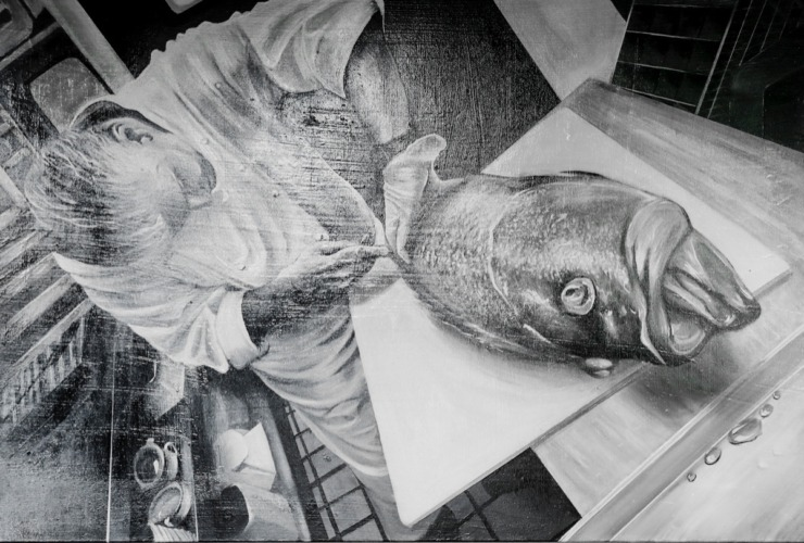 Emily LaForce, a sous chef at River Oaks and an aspiring artist, painted a portrait of Chef José Gutierrez breaking down a fish that adorns a restaurant wall on Tuesday, July 28, 2020. (Mark Weber/Daily Memphian)