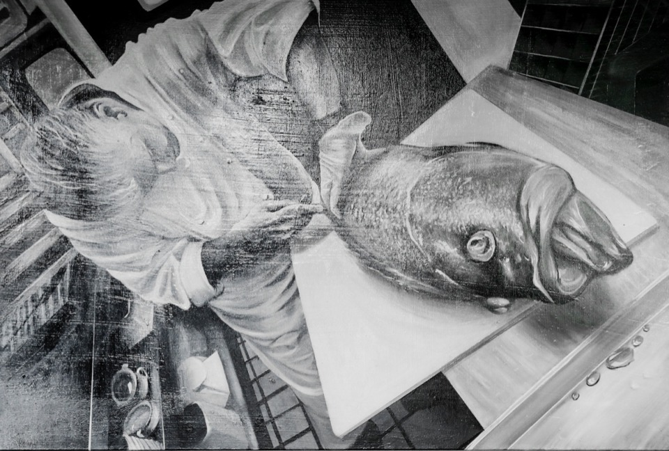 <strong>Emily LaForce, a sous chef at River Oaks and an aspiring artist, painted a portrait of Chef Jos&eacute; Gutierrez breaking down a fish that adorns a restaurant wall on Tuesday, July 28, 2020.</strong> (Mark Weber/Daily Memphian)