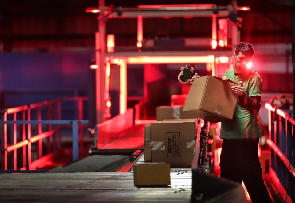 <strong>A worker at the FedEx Ground Hub in Olive Branch re-tapes a package before it moves through a scanning tunnel at the FedEx Ground Hub.</strong> (Jim Weber/Daily Memphian file)