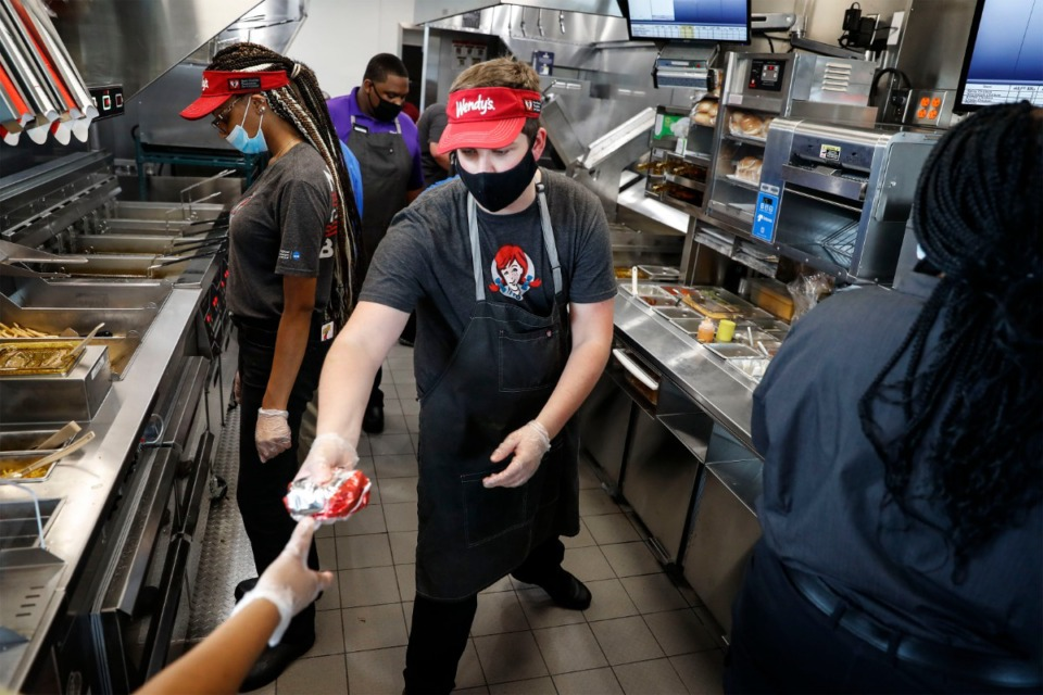 <strong>Wendy&rsquo;s employee Caleb Johnson (middle) hands off a cheeseburger on opening day of the fast-food restaurant&rsquo;s new location in Arlington Thursday, July 30, 2020.</strong> (Mark Weber/Daily Memphian)