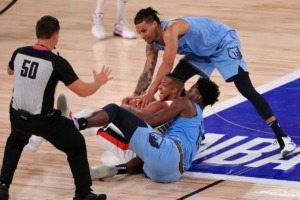 <strong>Memphis Grizzlies&rsquo; Jaren Jackson Jr. (13) and Portland Trail Blazers CJ McCollum (3) compete for a loose ball during the second half of an NBA game Friday, July 31, in Orlando. The Grizzlies lost in overtime, 140-135.</strong> (Mike Ehrmann/Associated Press)