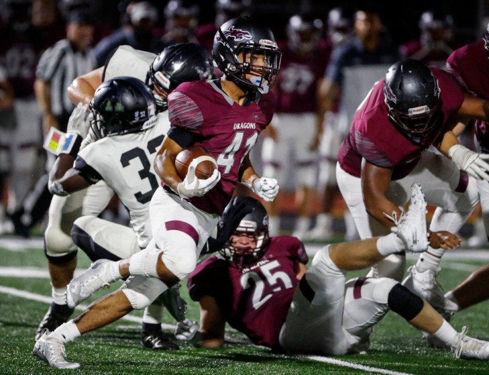 <strong>Collierville running back Duple Travillion (middle) runs past the Houston defense during their high school football game on Oct. 10, 2019. High school sports in Collierville and Arlington will move forward, according to school officials.</strong> (Mark Weber/Daily Memphian file)