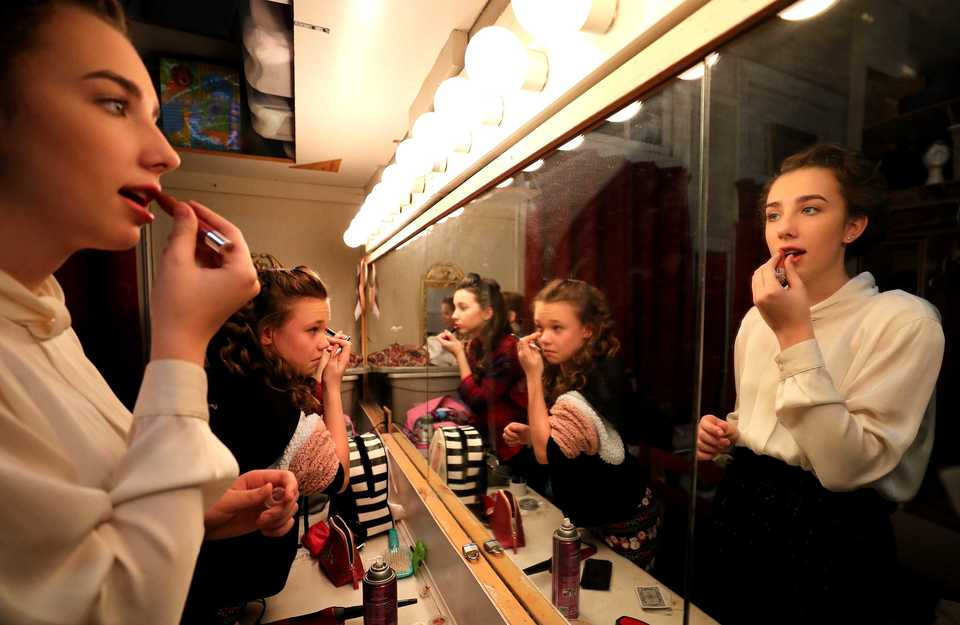"<strong>Jessica Ryan (right), Cecily Weiss (center) and Mary Parish (left) put on makeup as they prepare to head on stage for a performance of ""It's A Wonderful Life"" at the Germantown Community Theatre.</strong> (Houston Cofield/Daily Memphian)"