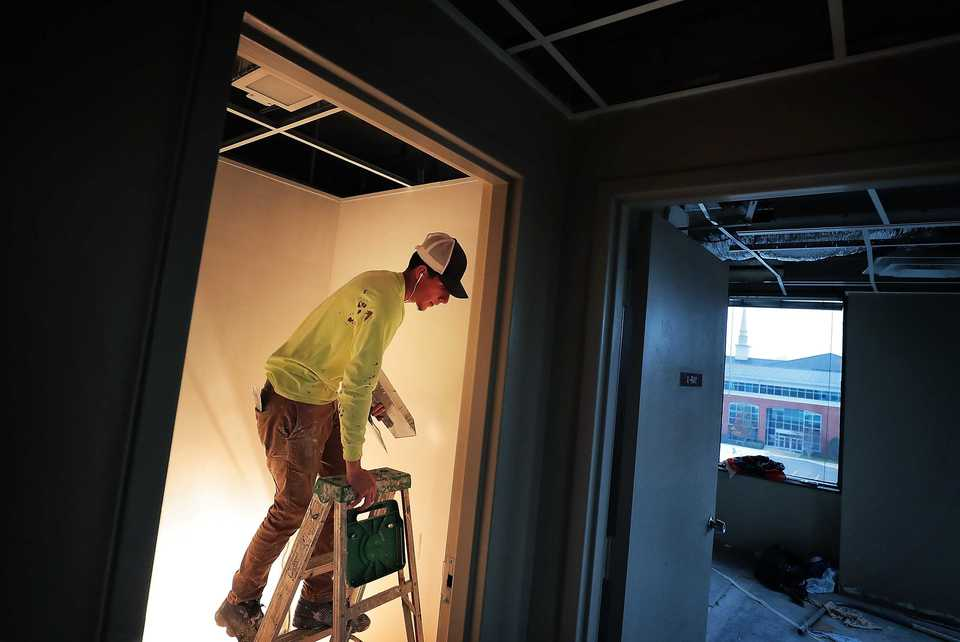 <strong>Edgar Sotelo installs drywall in an office at Poplar Towers on Dec. 5, 2018. Building owner Faropoint Ventures is in the process of renovating the 45-year-old office building in the middle of Memphis&rsquo; newest, most upscale and expensive offices. </strong>(Jim Weber/Daily Memphian)