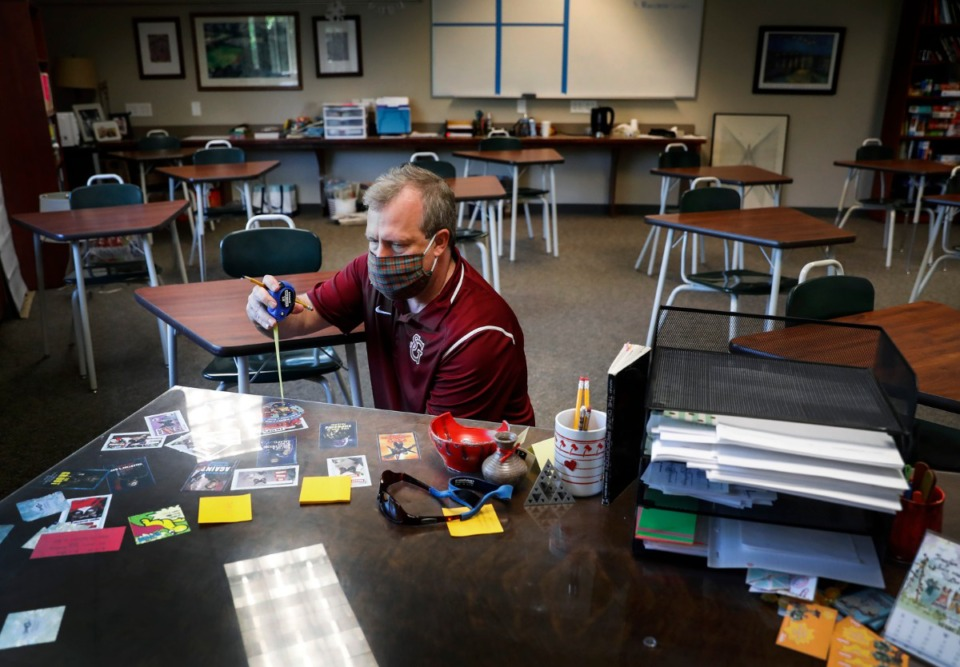 <strong>Gil Brandon, St. George&rsquo;s Assistant Head of School for Institutional Advancement measures his wife&rsquo;s classroom desk on Friday, June 11, 2020. The desk will be removed to create the necessary space for social distanced learning at the school.</strong> (Mark Weber/Daily Memphian file)