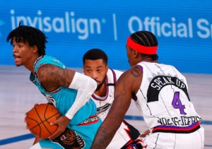 <strong>Memphis Grizzlies' Ja Morant, left, drives between Toronto Raptors' Rondae Hollis-Jefferson (4) and Norman Powell, center, during the second quarter of an NBA basketball game Sunday, Aug. 9, 2020, in Lake Buena Vista, Fla.</strong> (Kevin C. Cox/AP)