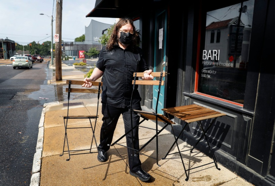 <strong>Bari Ristorante e Enoteca waiter Brandon Noe sets up outdoor seating on Tuesday, Aug. 11. The Midtown restaurant has asked for street seating, an allowance city administrators announced they would consider on a case-by-case basis.</strong> (Mark Weber/Daily Memphian)