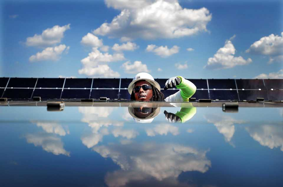 <strong>Detarius Rhodes installs new panels at the new 421-acre solar farm under construction east of Millington on Sept.18, 2018. Billed as the largest solar farm in the state with over a half million panels, the Silicon Ranch facility is the kind of new business Millington is looking to draw as it tries to leverage its airport and other new retail properties to lead it away from the years as a pit stop for young sailors and toward more higher paying jobs.</strong> (Jim Weber/Daily Memphian)