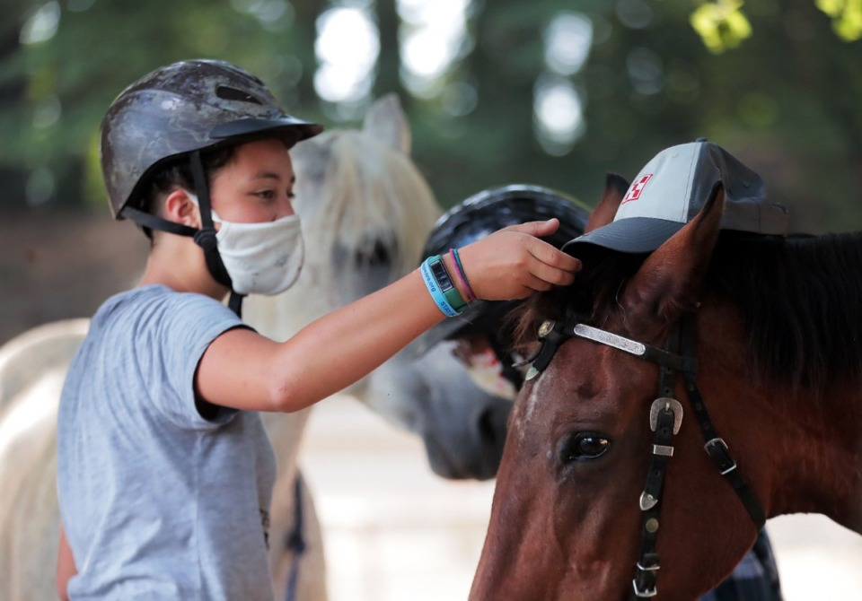 <strong>Anna Mauwong playfully puts her hat on her horse Annie while getting ready to go on a ride July 15, 2020.</strong> (Patrick Lantrip/Daily Memphian)