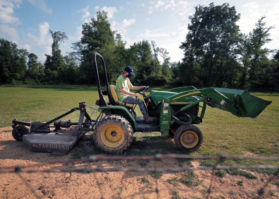 <strong>Celina Owens mows the pasture at ARK Farms to help keep the grounds free from predators and parasites July 15, 2020.</strong> (Patrick Lantrip/Daily Memphian)