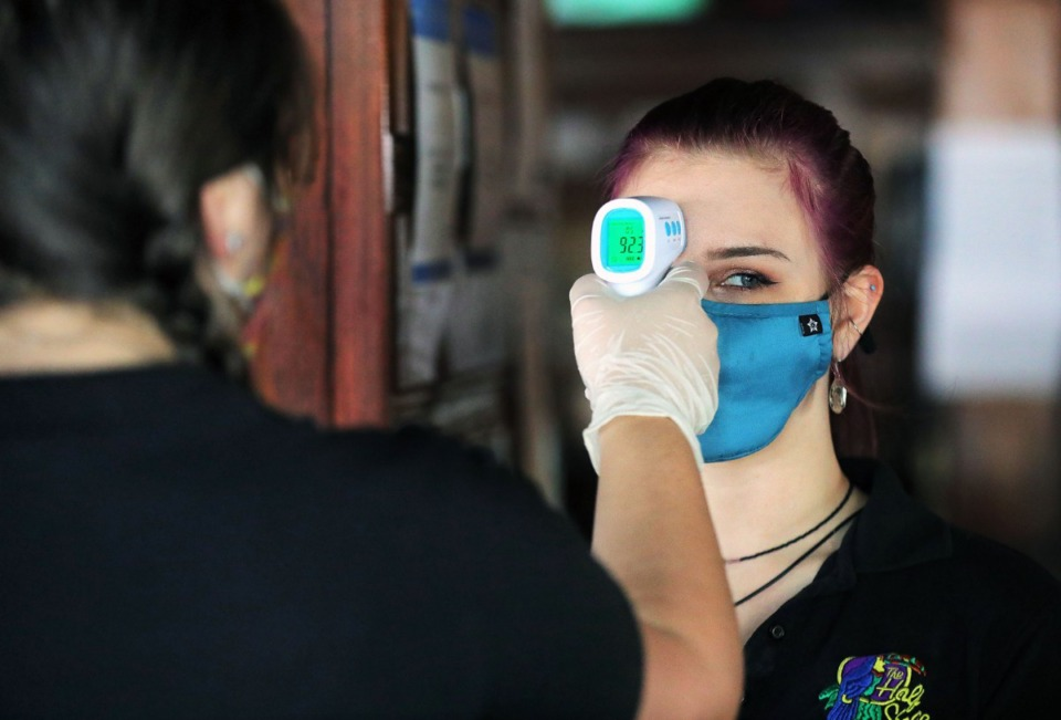 <strong>Brittaney Gulley (left) checks the temperature of fellow Half Shell employee Terra Sullivan May 4, 2020. Temperature checks and masks are among the tools businesses use to protect employees.</strong> (Patrick Lantrip/Daily Memphian)
