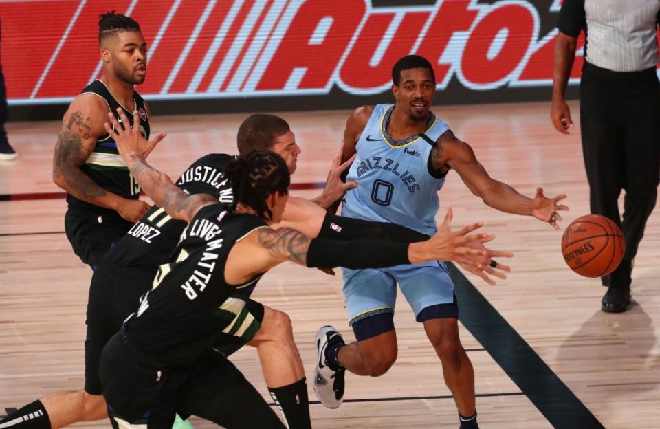 <strong>Memphis Grizzlies guard De'Anthony Melton (0) passes against Milwaukee Bucks center Brook Lopez (11) and forward D.J. Wilson (5) during an NBA basketball game Thursday, Aug. 13, 2020, in Lake Buena Vista, Fla.</strong> (Kim Klement/Pool Photo via AP)