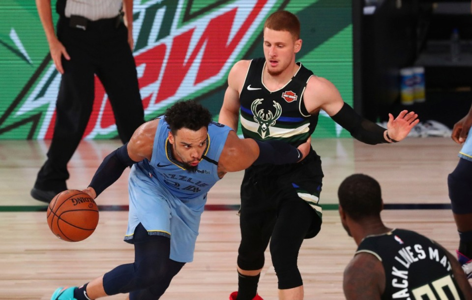 <strong>Memphis Grizzlies guard Dillon Brooks (24) drives against Milwaukee Bucks guard Donte DiVincenzo (top right) in their game Thursday, Aug. 13, in Lake Buena Vista, Fla. The Grizzlies won 119-106, and are headed to the NBA&rsquo;s first Western Conference playoff play-in.</strong> (Kim Klement/Associated Press)