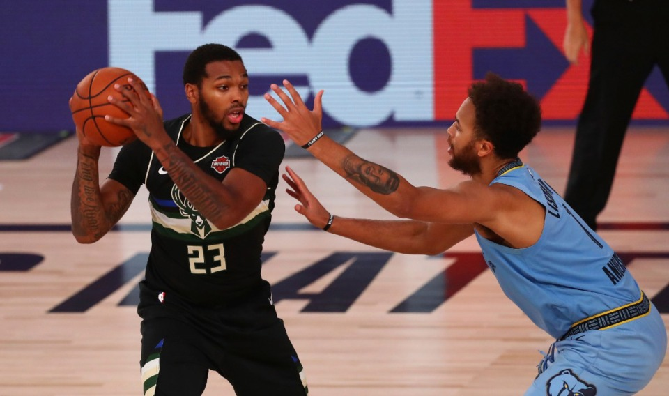 <strong>Milwaukee Bucks guard Sterling Brown (23) holds the ball away from Memphis Grizzlies forward Kyle Anderson (1) Aug. 13, 2020, in Lake Buena Vista, Fla.</strong> (Kim Klement/Pool Photo via AP)